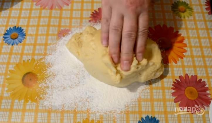 3.Стол посыпаем мукой, выкладываем тесто, обминаем его и руками раскатываем в пласт.