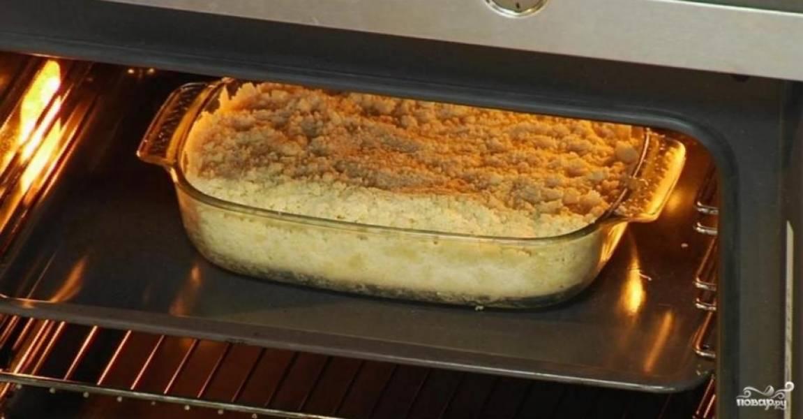 4.В небольшой емкости нагрейте воду, разведите в ней оставшийся сахар и крахмал. Постоянно помешивая, продолжайте нагревать до получения густой клейкой массы. Добавьте ванильный сахар и перемешайте. Яблоки залейте полученной смесью, перемешайте и выложите в форму поверх основы. Разровняйте и равномерно засыпьте оставленной крошкой.