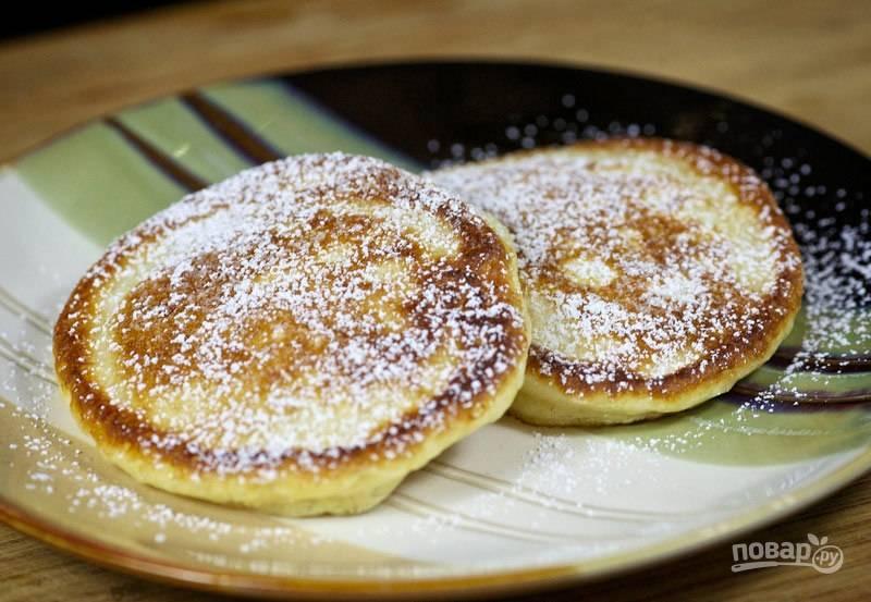 Подавайте оладьи со сметаной, вареньем, медом или просто посыпанными сахаром.