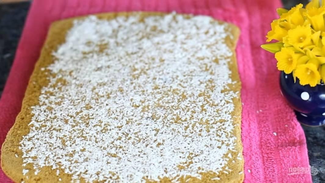 7.Накройте бисквит влажным полотенцем, переверните, снимите пергаментную бумагу и посыпьте кокосовой стружкой.