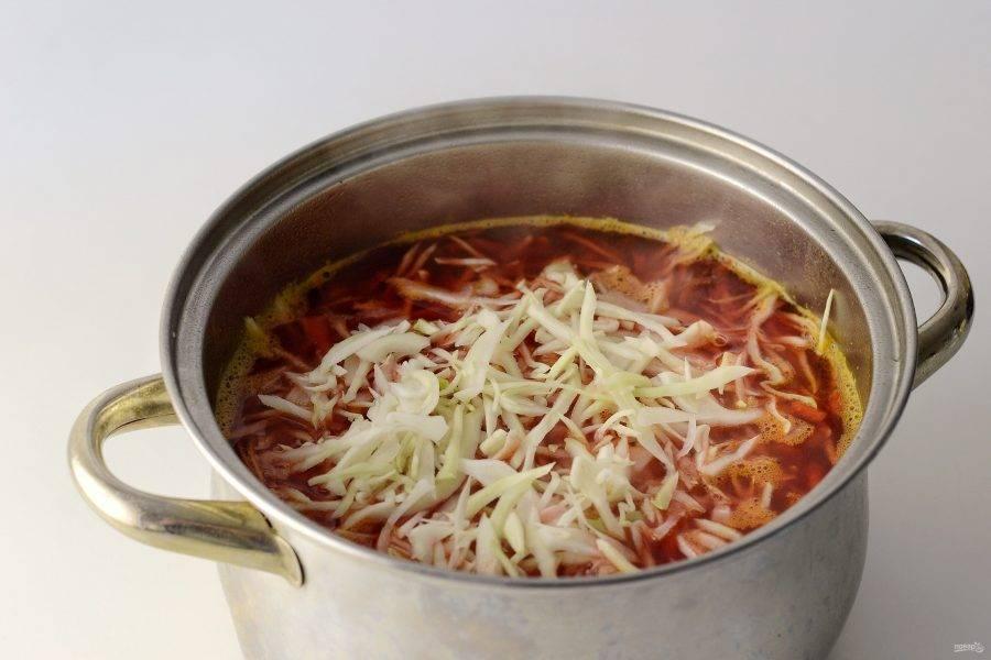 Добавьте в кастрюлю тушеные овощи и мелко нашинкованную капусту. Посолите и поперчите. Доведите до кипения и варите суп 10-15 минут.