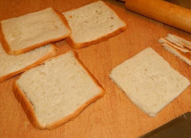 Обрежьте корочку у хлеба и раскатайте его скалкой.