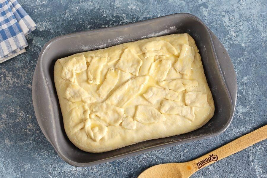 Теперь свисающими концами теста накройте пирог со всех сторон. Излишки можно обрезать ножницами и выложить сверху. Смажьте пирог со всех сторон оставшимся маслом и выпекайте в духовке при температуре 180-200 градусов около 25 минут.