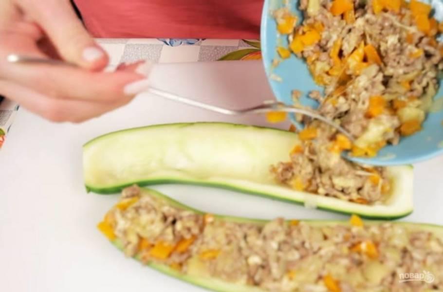 3. Далее добавьте нарезанный болгарский перец и воду, чтобы смесь стала более сочной. Переложите начинку в миску и добавьте мелко натертый сыр, мякоть кабачка. Перемешайте и нафаршируйте этой массой ранее подготовленные кабачки.