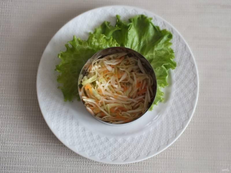 В салат можно добавить заправку и перемешать. Но лучше подать такой салат индивидуально. Возьмите сервировочное кольцо. Уложите на тарелку салатный лист, поставьте кольцо. Положите слой белокочанной капусты с морковью и луком.
