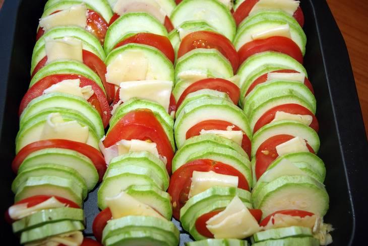 Сыр нарезаем ломтиками. Теперь разложите на противне, чередуя с друг другом, кружочки кабачков, помидоров и сыр. Противень предварительно смажьте растительным маслом.