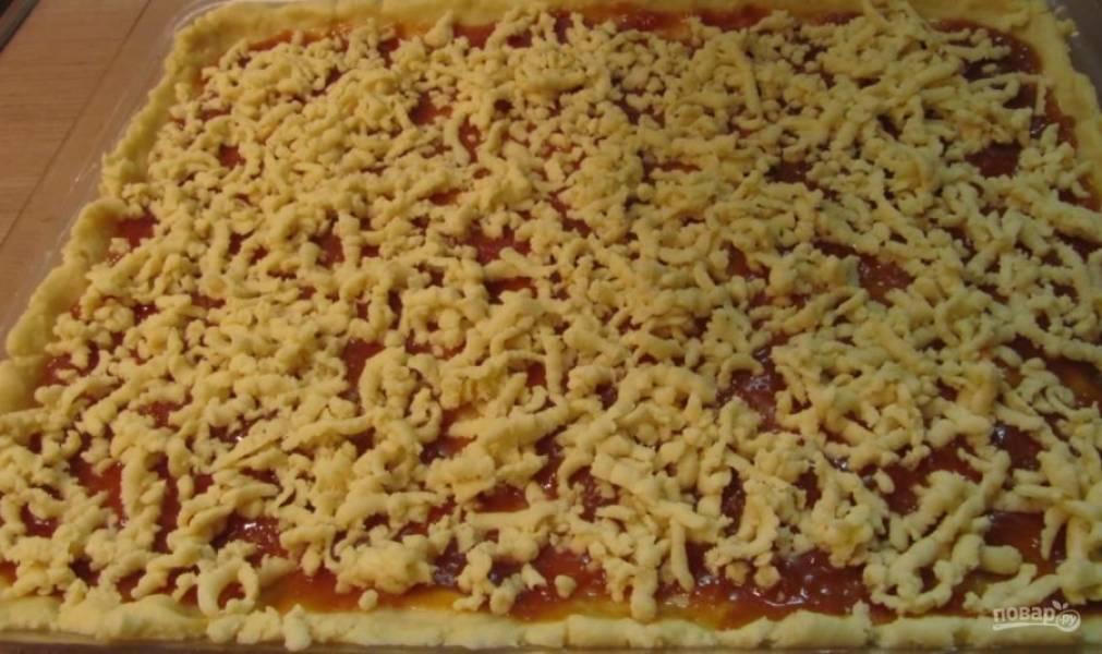 Тесто достаньте из морозилки и натрите на терку сверху на пирог.
