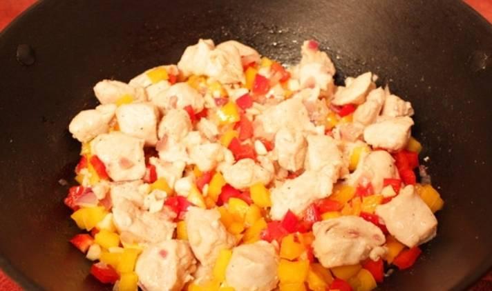 Добавьте к курочке перец и помидоры, порезанные кубиками. Также можно добавить измельченный чеснок. Тушим на среднем огне 10 минут, периодически помешивая.