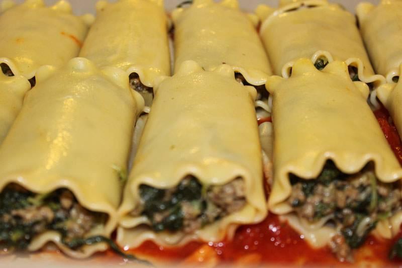 4. На дно жаропрочной формы выложить пару ложек томатного соуса. Нафаршировать каннеллони остывшей начинкой и выложить в форму.