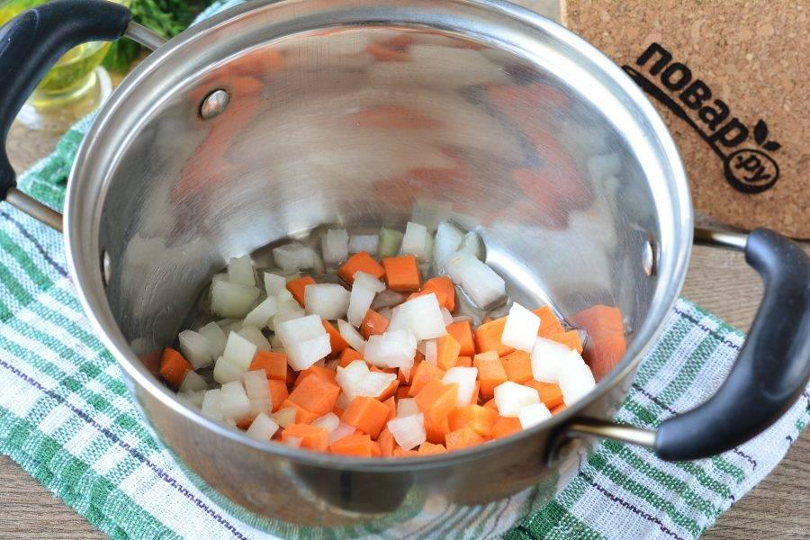 Немного разогрейте масло в кастрюле, всыпьте лук и морковку. Пассеруйте 5 минут.
