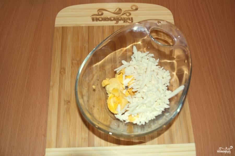 Отварите куриные яйца вкрутую. Остудите их. Очистите и разрежьте каждое яйцо пополам. Извлеките половинки желтка. Поместите в мисочку. Натрите на терке брынзу.