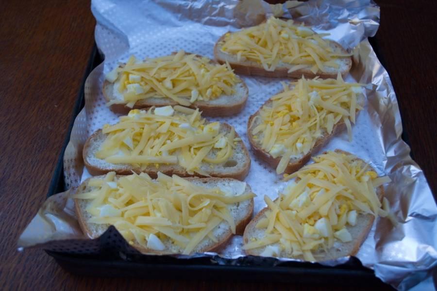 В полученную смесь добавьте выдавленный через пресс чеснок. Уложите яично-сырную смесь на каждый кусочек батона поверх масла.