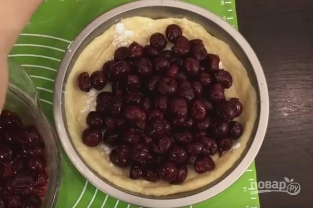 9. Переложите тесто в форму для выпекания, поднимите тесто на бортики, прихлопывая его пальцами. Сверху присыпьте слегка крахмалом и выложите всю вишню, слегка отжимая с нее сок. Начинка должна лежать плотно и равномерно.