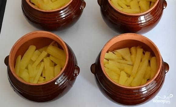 1. Первым делом очистите картофель и нарежьте мелкими брусочками. Подсолите немного по вкусу. Выложите на дно горшочков.