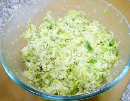 Теперь добавляем к кабачкам тертый на мелкой или средней терке сыр, смешанные с крахмалом овсяные хлопья, измельченный чеснок, нарезанный мелко зеленый лук, молотый перец и соль по вкус. Тщательно перемешиваем все до однородного состояния.