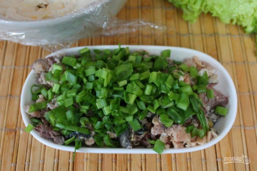 Рыбу разминаем вилкой и добавляем к ней нарезанный мелко зеленый лук.
