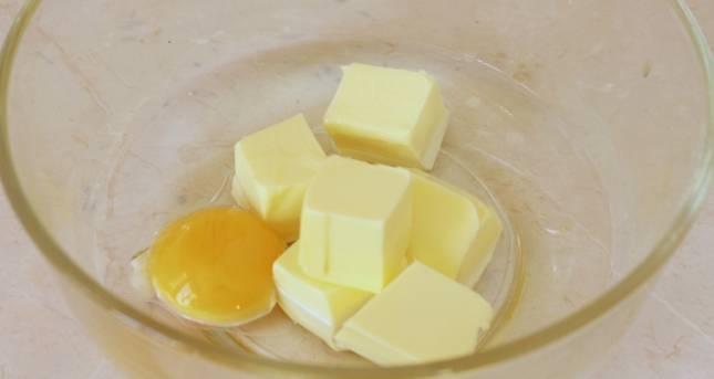 Соединяем размягченное сливочное масло, желток и подсолнечное масло. Перемешиваем до однородности.