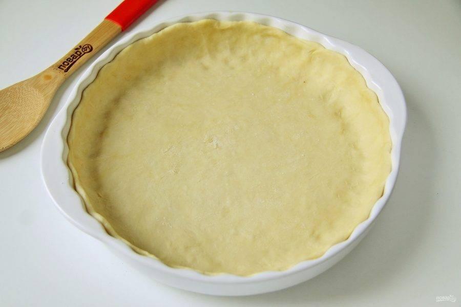 Достаньте тесто и разделите его на две части. Одна должна быть чуть больше, вторая немного поменьше. Раскатайте большую часть и перенесите ее в форму для выпечки. У меня форма в диаметре 26 см. Сформируйте руками высокие бортики.