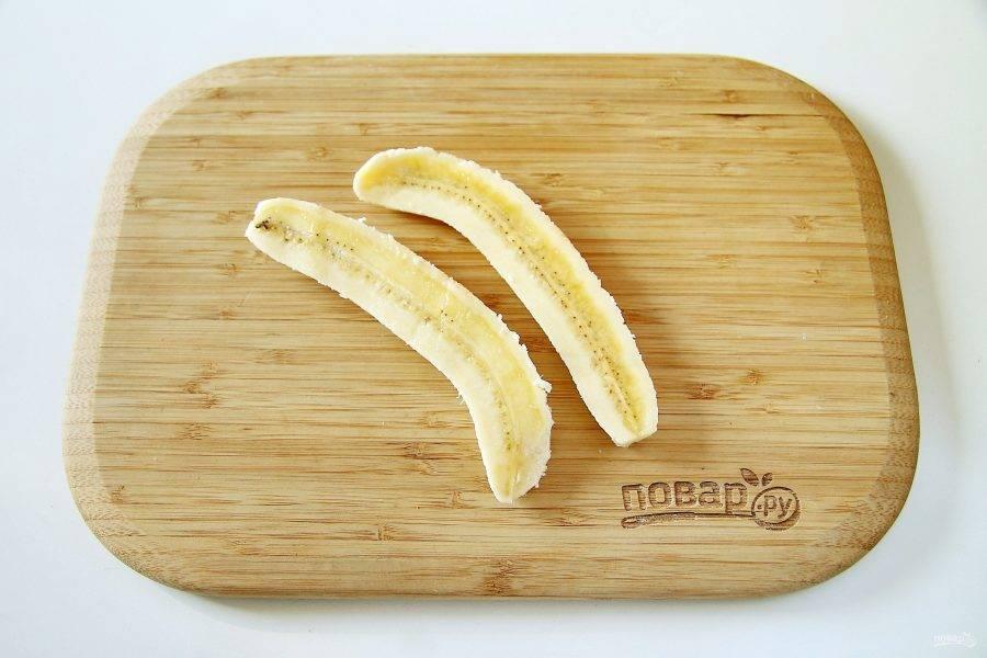 Банан очистите и разрежьте вдоль пополам. Чтобы он не потемнел можно смазать его соком лимона.
