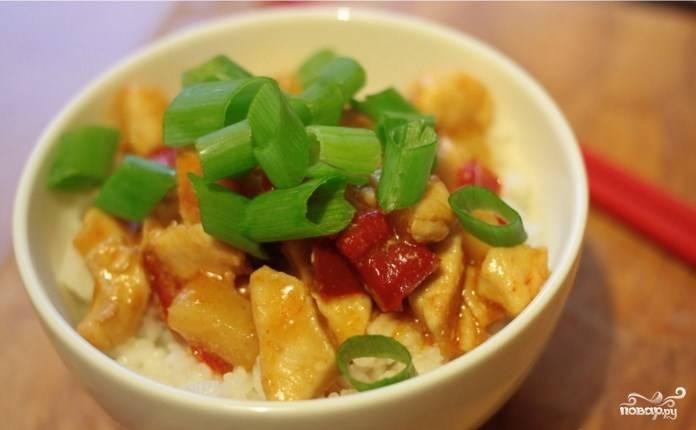 Зеленый лук порежьте мелко, добавьте к нему кунжутное масло (это не обязательно). Подавайте готовую курицу в кисло-сладком соусе с рисом и луком.