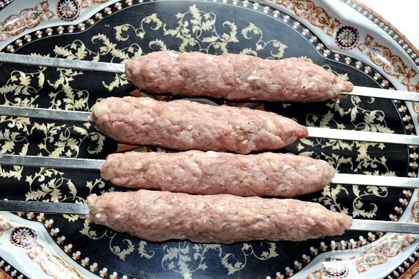 Отщипните кусочек фарша, скатайте из него условную котлетку. Поместите на шампур и распределите, формируя вот такие колбаски на шампурах.