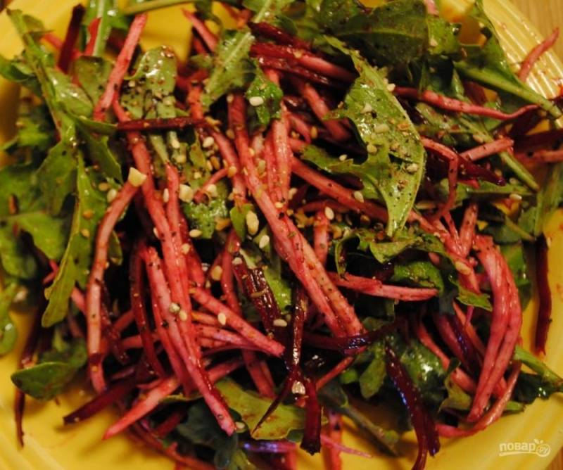 3.Вымойте рукколу и добавьте ее в миску к овощам, еще раз перемешайте и подавайте салат к столу, украсив его семенами кунжута.