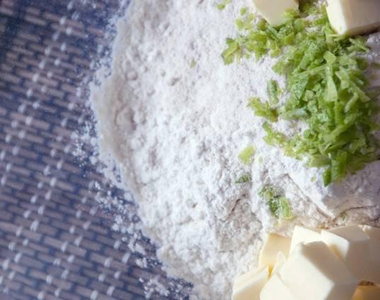 Смешайте в миске сахар, муку, чайную ложку цедры, щепотку соли, масло, столовую ложку сока и яичный желток. Замесите тесто.