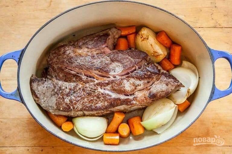2.Разогрейте кастрюлю с оливковым маслом, выложите мясо и обжаривайте его со всех сторон до золотистой корочки. Выложите вокруг мяса лук и морковь.