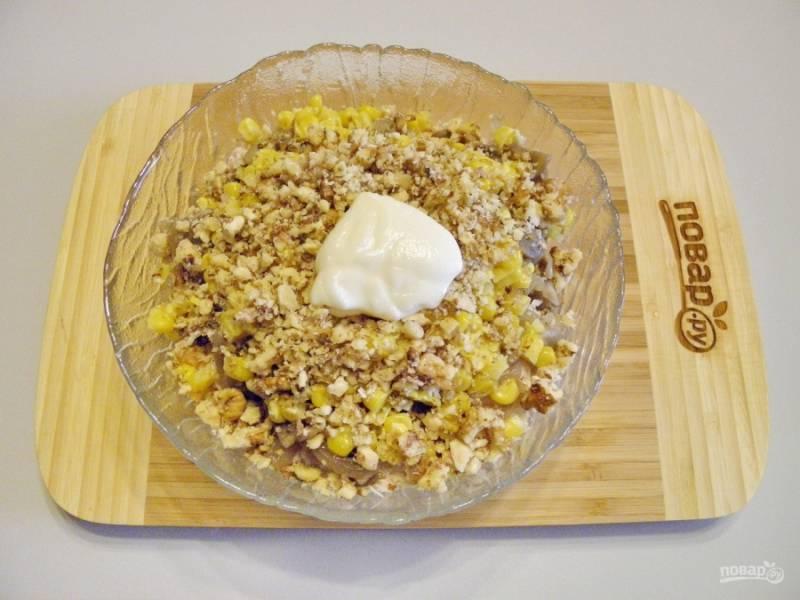 Орехи растолките в ступке, положите в салат. Заправьте его не большим количеством майонеза. Соль и перец черный молотый — по вкусу.