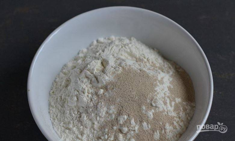 Муку просейте через сито несколько раз, чтобы она насытилась кислородом. Тогда булочки получатся воздушными. Поместите ее в миску, добавьте сухие дрожжи и соль.