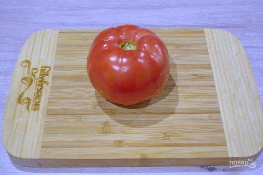 Свежий помидор промойте под проточной водой. Удалите место крепления плодоножки и нарежьте помидор на небольшие кусочки.
