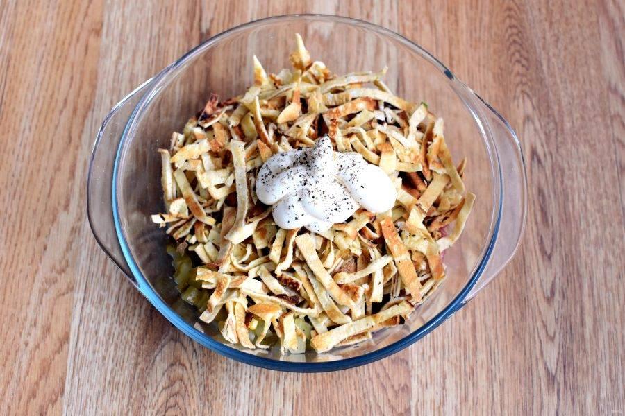 Добавьте яичные блинчики, нарезанные короткой соломкой. Заправьте салат смесью майонеза со сметаной и поперчите по вкусу. Хорошо перемешайте.