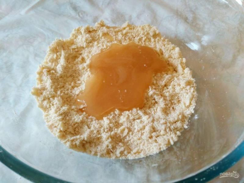 Руками разотрите в крошку масло и сухие компоненты, затем добавьте мёд.
