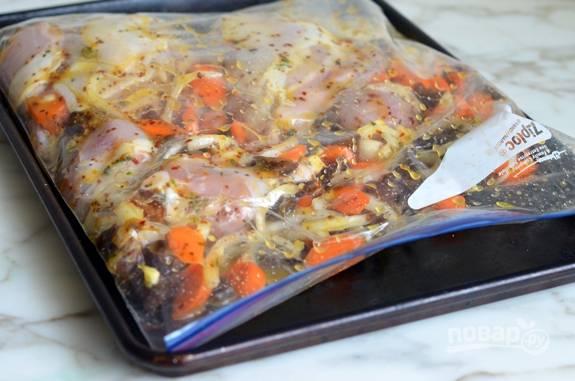 2. Курицу разберите на части. Выложите их в плотный закрывающийся пакет для маринования. Добавьте лук полукольцами, измельчённые финики, морковь кружками, и, самое главное, маринад из первого шага.