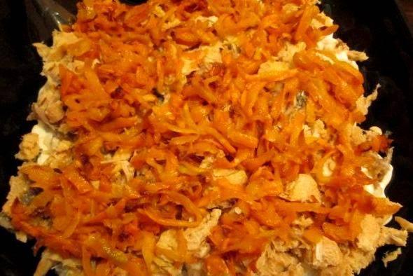 Морковь трем на крупной терке и обжариваем в растительном масле до золотистого цвета, солим и перчим ее. Над рыбой делаем слой из моркови, который также смазываем майонезом.