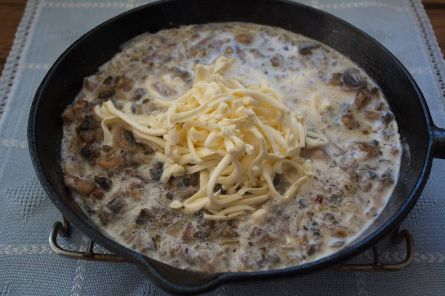 Обжарьте грибы с луком до готовности. Влейте молоко. Натрите на терке плавленый сырок. Быстро вилкой или венчиком перемешайте сырок с молоком и грибами. Разминайте кусочки сыра до полного его растворения в молоке. Молоко будет кипеть на среднем огне. Огонь лучше сделать поменьше, но постоянно размешивая, полностью растворить сырок.