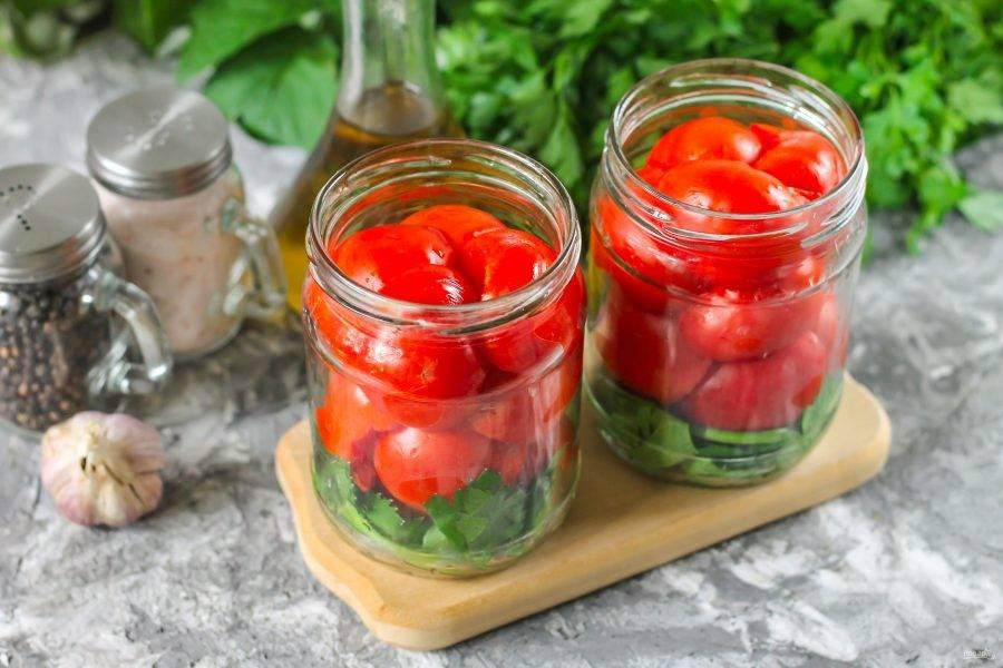 Помидоры промойте в воде, разрежьте каждый из них пополам и вырежьте зеленые черенки. Выложите томатную нарезку в банки до самого верха как можно плотнее.