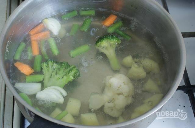 После закипания добавьте в воду брокколи, цветную капусту и фасоль кусочками. Варите овощи в течение 7 минут.
