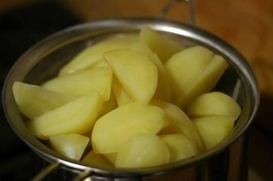 5. Картошку почистите, нарежьте четвертинками, выложите в кастрюлю, залейте водой и поставьте на огонь. Снимите и откиньте на дуршлаг, как только вода закипит.