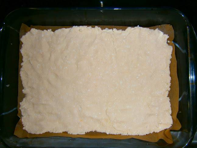 Форму для выпечки застилаем пергаментом. Ровным слоем выкладываем творожное тесто.