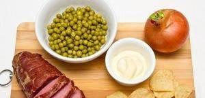 Основные ингредиенты: ветчина, лук, чипсы, горошек и майонез.
