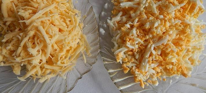 8. Сыр и куриные яйца натрите на терке в разные миски.
