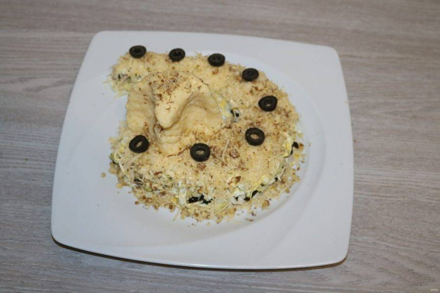 Посыпьте салат измельчёнными грецкими орехами. Выложите кружочки маслин.