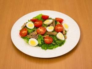 Перекладываем листья салата и мясо на тарелку. Сверху кладем помидоры и яйца.