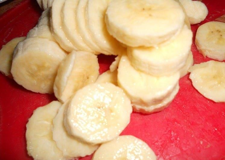 Бананы нарежьте и полейте лимонным соком.