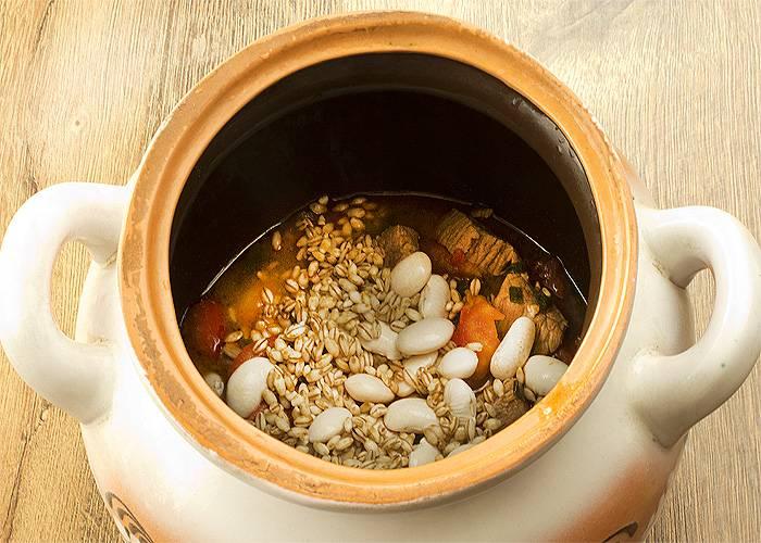 Затем в горшочек кладем перловку, фасоль, измельченный помидор. Добавляем соль, перец и любимые приправы. Заливаем водичкой, но оставляем место для компонентов, которые разбухнут и подрастут во время приготовления. Закрываем горшочек и отправляем обратно в духовку на 40-50 минут.
