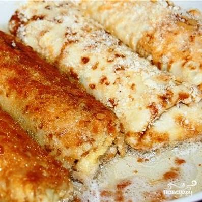 Полученные блинные рулеты сперва обмакиваем во взбитом яйце, затем обваливаем в панировочных сухарях, и - на сковороду с разогретым растительным маслом. Обжариваем до золотистой корочки.