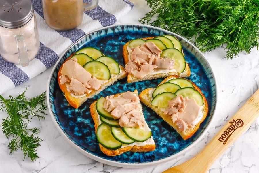 Вскройте консервы с печенью трески, аккуратно извлеките печень из масла и выложите на незаполненные половинки брускетт.