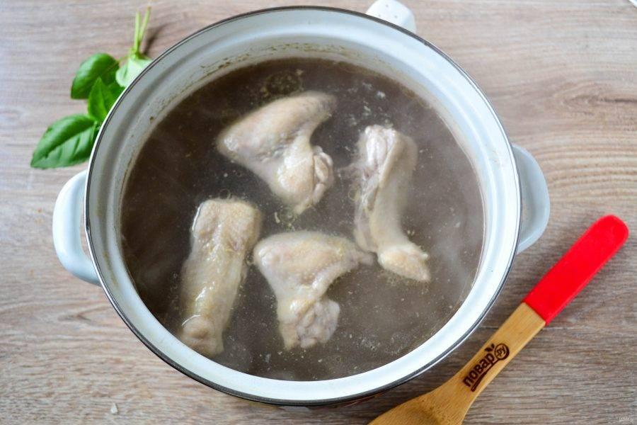 Первым делом необходимо приготовить куриный бульон. Я буду использовать куриный суп-набор. Наберите в кастрюлю 4,5 литра воды, доведите до кипения, затем отправьте в кастрюлю части курицы. Когда вода закипит, будет появляться пенка, ее необходимо снимать, пока она не перестанет появляться. Посолите и поперчите бульон и варите в течение 20-30 минут. Если используете домашнюю курицу, то варить бульон необходимо не менее часа.