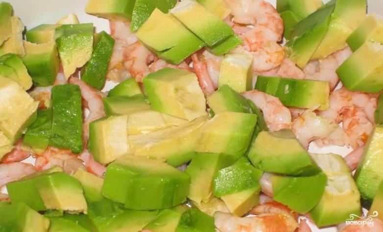 Авокадо промойте и нарежьте небольшими кусочками, сбрызните его лимонным соком. Соедините с креветками.